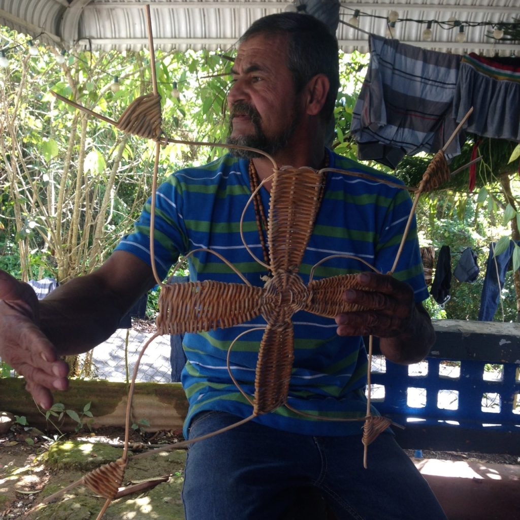 Edwin Marcucci holding a cross made with 'bejucos' (vines) from the Cupey Tree. Photo taken at his home in Adjuntas, PR